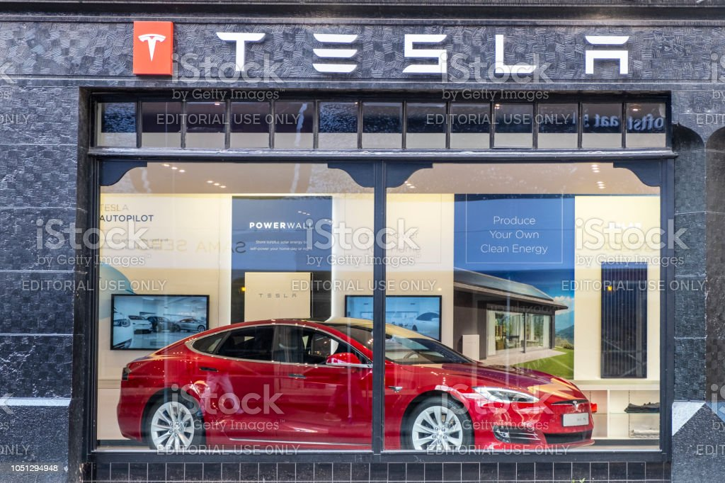 Tesla showroom in Amsterdam with a red Tesla Model S electric car on display inside Tesla showroom located on the corner of the Hobbemastraat and PC Hooftstraat in Amsterdam. A Red Tesla Model S full-sized electric five-door hatchback is on display inside. People in the foreground are looking at the car. Amsterdam Stock Photo