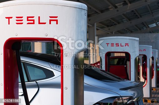 Shenzhen. China - November 15, 2016: Tesla model S cars charging their battery with the Tesla supercharger station near Shenzhen sport arena. Tesla is an American automotive and energy storage company that designs, manufactures and sells luxury electric cars