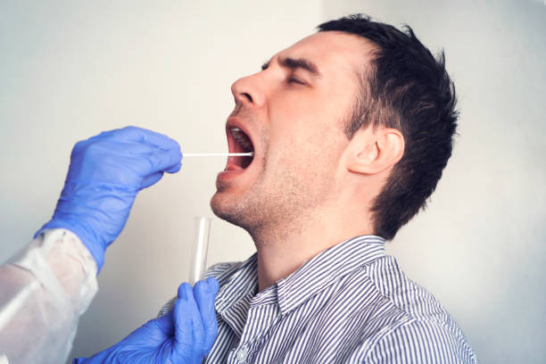 DNA test. Doctor Doing Coronavirus covid 19 Test For male Patient. Taking a saliva sample from a man. Collection of mucus from the throat for research in the laboratory. stock photo