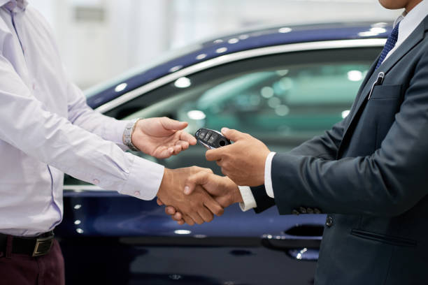 Test drive concept Salesman giving car keys to customer and shaking his hand car salesperson stock pictures, royalty-free photos & images