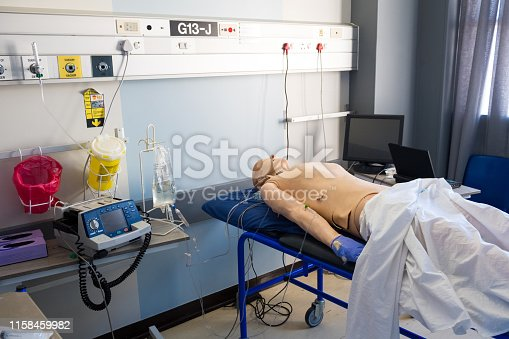 High angle view of test dummy on hospital bed. Male mannequin is in ward. Interior of medical clinic.