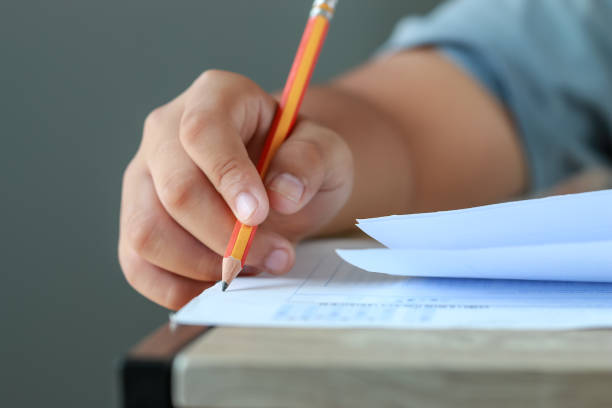 test exam for education in school concept : University student holding pencil notes paper on answer sheet at lecture chair for taking exams in examination classroom. Assessment learning in class ideas stock photo