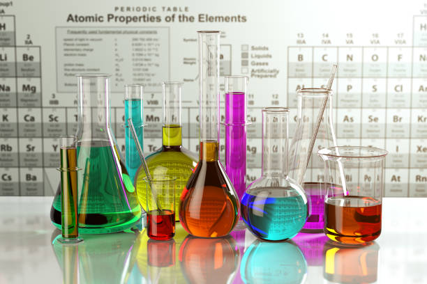 Test glass flasks and tubes with colored solutions on the periodic table of elements. Laboratory glassware. Science chemistry and research concept. stock photo