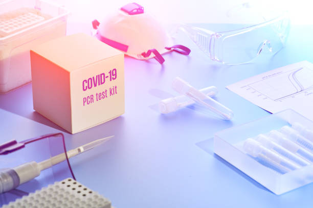 Test kit to detect novel COVID-19 coronavirus in patient samples. RT-PCR kit reagents convert viral Covid19 RNA to DNA and amplify region of viral DNA specific for 2019-nCov. Neon glow, purple light. stock photo