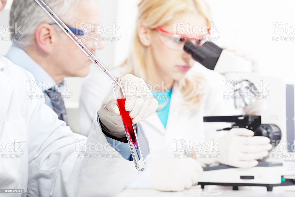 Test Tube Chemistry Sample with two scientists in background royalty-free stock photo