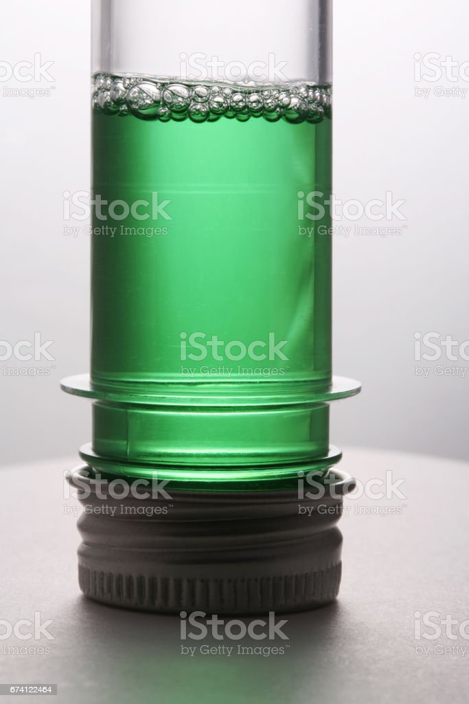 Test tube with a green liquid on a white background 免版稅 stock photo