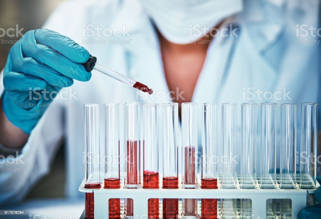 Test tubes containing red liquid with more being added stock photo