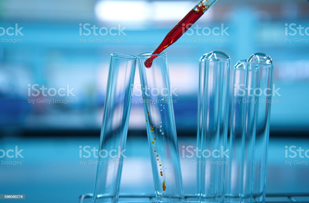 test tubes with orange drop in lab science royalty-free stock photo