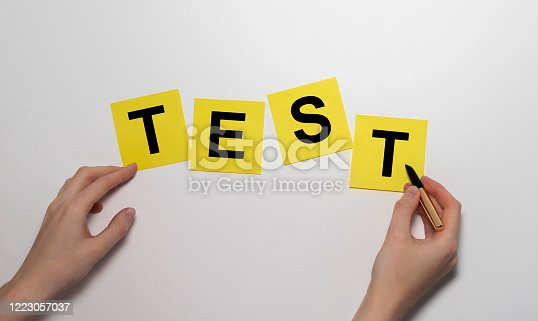 istock Test word on yellow sticker notes on white wall with female hands 1223057037