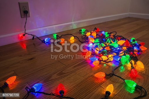 Testing a string of various colored LED faceted Christmas tree lights before they are strung up around the house or on a Christmas tree. The lights are plugged into a household electrical outlet and are lying on a hardwood floor in a heap inside of a home.