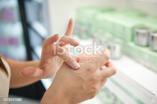 Woman testing hand cream in cosmetic store