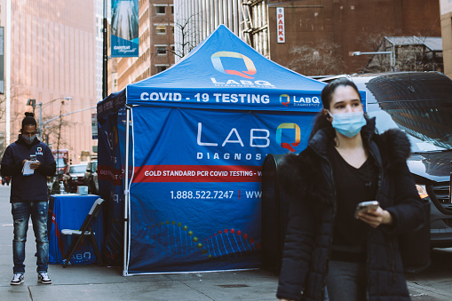 Testing tent in Manhattan on the corner of Wall Street and Water street during Coronavirus outbreak. Woman in face covering is in the foreground.