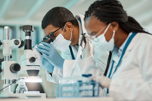 Shot of a young scientist using a microscope while working alongside a colleague in a lab
