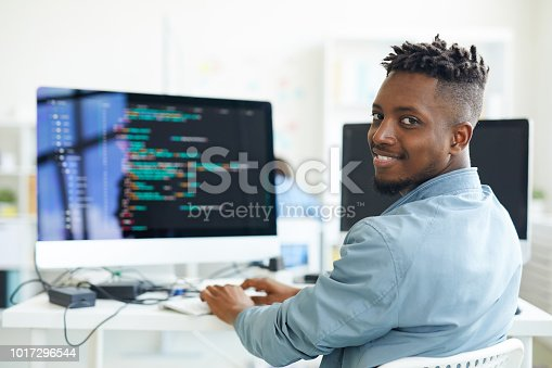 Happy guy looking at you while sitting by workplace and working with software