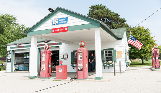 Dwight, USA - August 31, 2015: Texaco garage restored as tourist information and museum roadside attraction a with old faded Texaco Sky Chief fuel pumps and tourists entering to obtain information Dwight Illinois USA