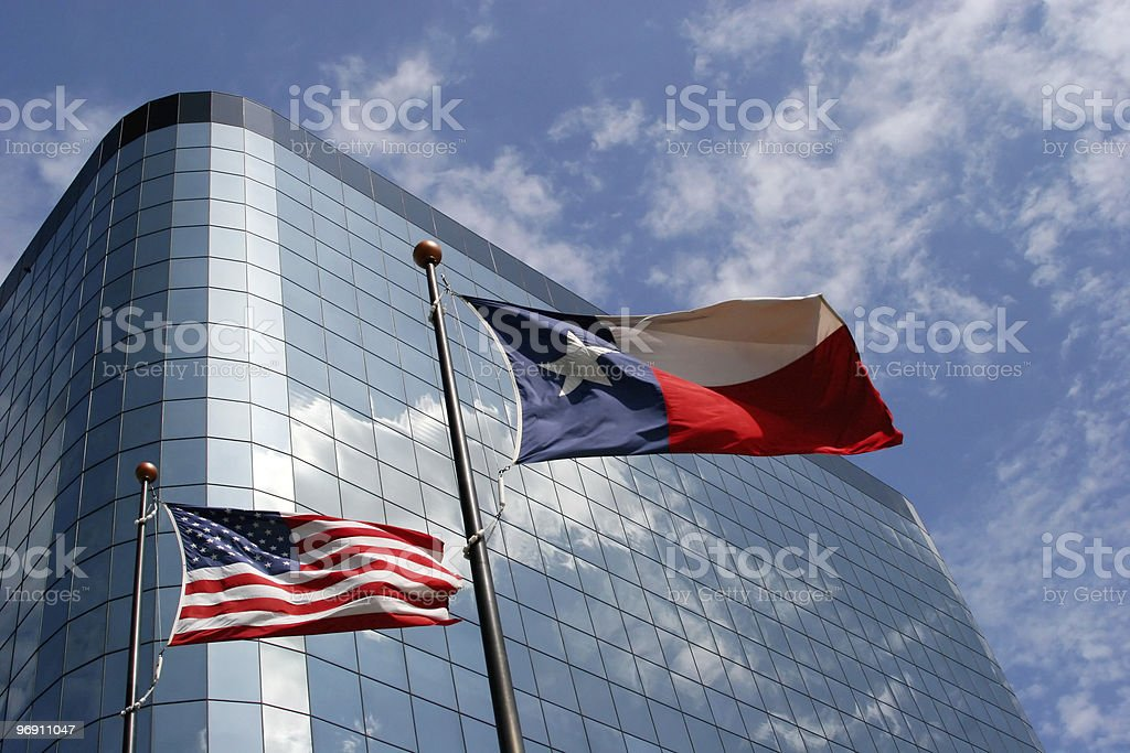 Texas and American flags by a skyscraper royalty-free stock photo