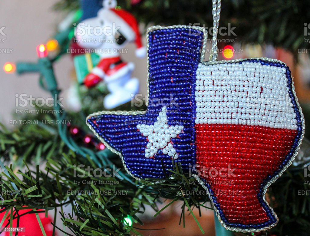 texas and snoopy ornaments on lighted christmas tree royalty free stock photo