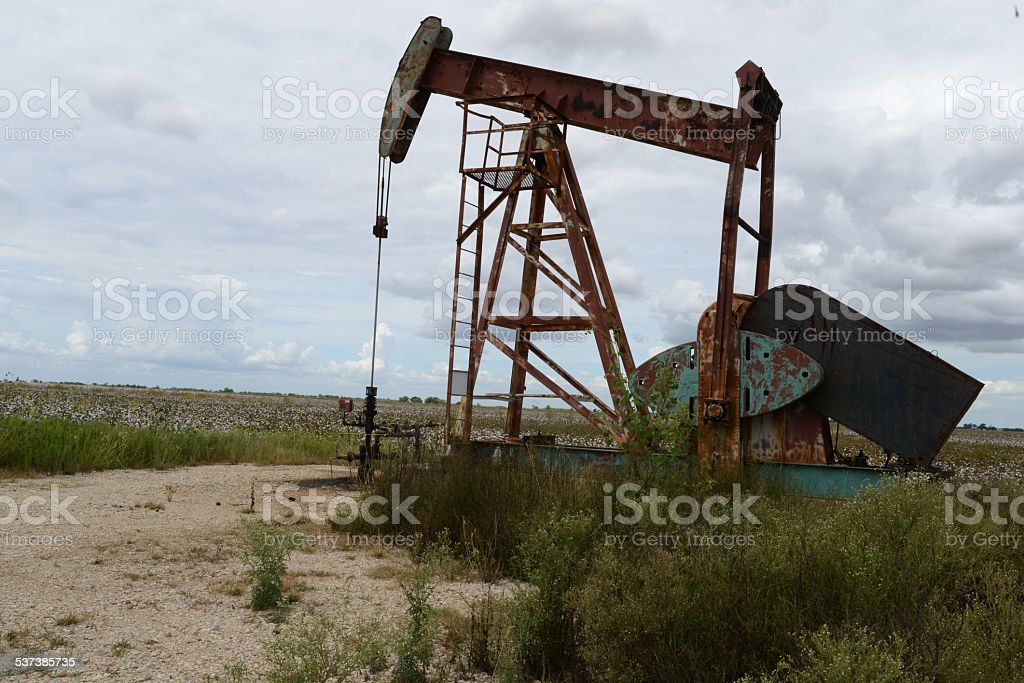 Texas cotton farm with Oil Pumping jack in rural field. stock photo