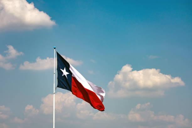 Texas flag flying in blue sky stock photo