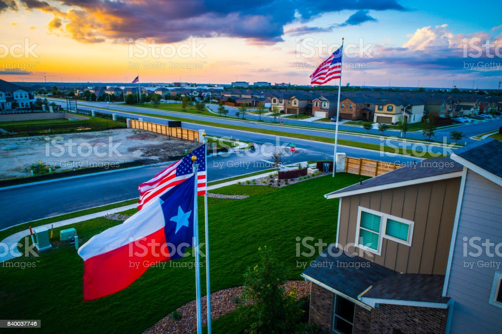Texas Flag flying in front of American Pride United States Flag Flying during amazing colorful Sunset stock photo
