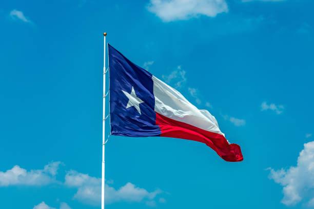 Texas flag on pole with sky stock photo