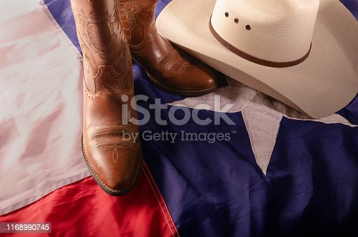 straw cowboy hat and cowboy boots surrounded by texas flag