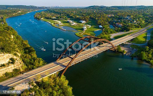 Aerial Drone views above the landmark Suspension bridge above 360 Bridge or Pennybacker Bridge - Texas Hill Country views above Pennybacker Bridge with Austin Texas Skyline far in the background