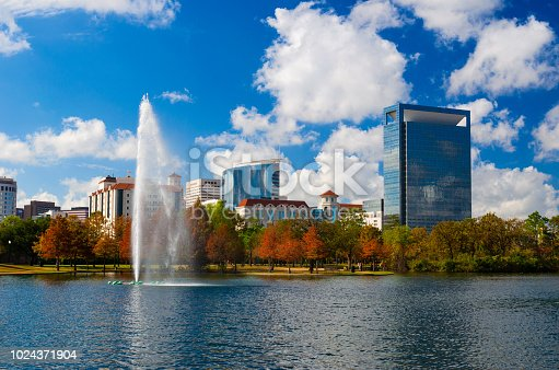 Texas Medical Center skyline during autumn with Hermann Park, including a lake with a fountain, in the foreground.