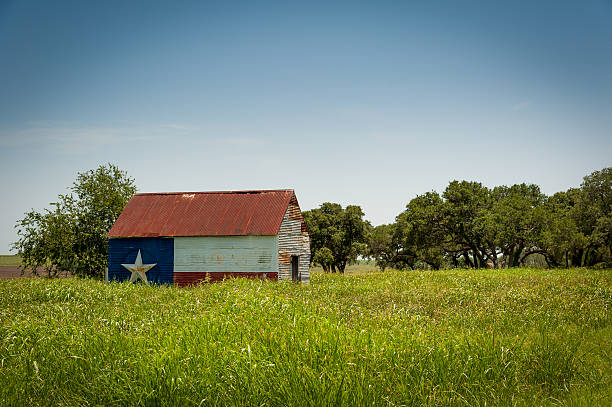 Texas Proud Barn Rustic barn with a Texas flag pained on the side ranch stock pictures, royalty-free photos & images