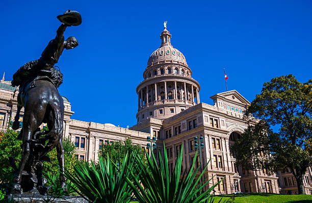 Texas State Capitol Building Cowyboy Austin Texas Texas State Capitol Building Cowyboy statue in central texas Austin Texas USA desert plants , Texas flag and American Flag , amazing Capitol building capital cities stock pictures, royalty-free photos & images