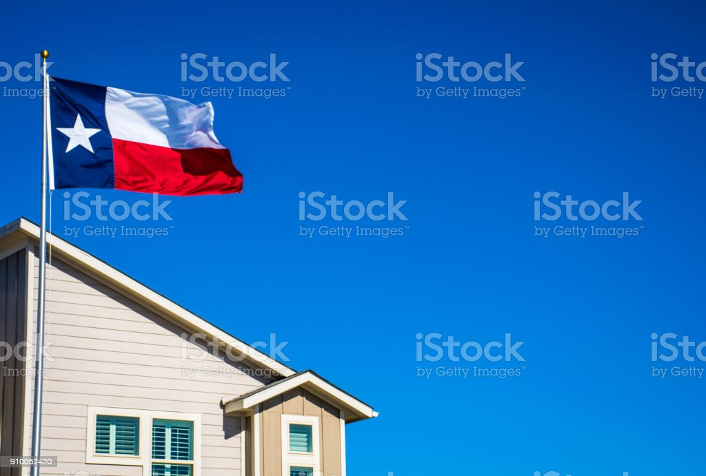 Texas State Flag the Symbol of the Lone Star State above Modern Brand New Suburban Home stock photo