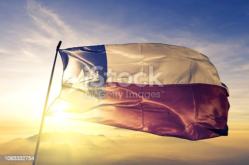 Texas state of United States flag on flagpole textile cloth fabric waving on the top sunrise mist fog