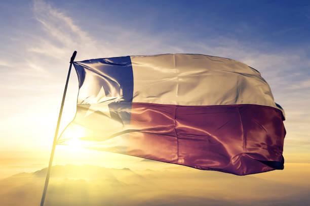 Texas state of United States flag textile cloth fabric waving on the top sunrise mist fog stock photo