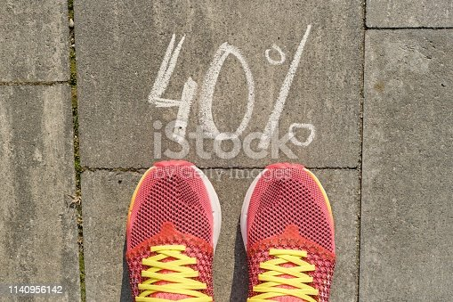 istock Text 40% written on gray pavement with woman legs in sneakers, view from above 1140956142