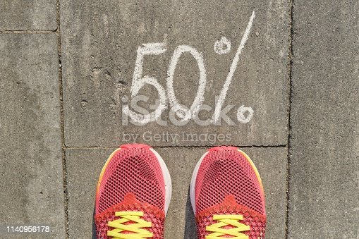 istock Text 50% written on gray pavement with woman legs in sneakers, view from above 1140956178