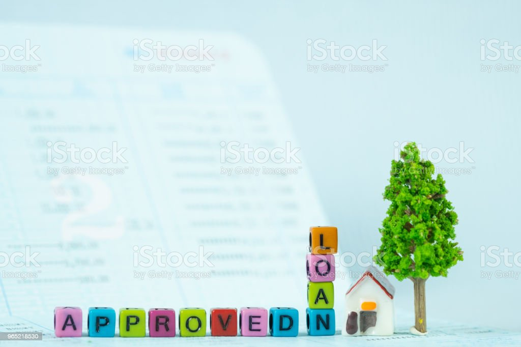 LOAN text and small model house and little tree with notebook, savings banking, loan for house and real estate concept. royalty-free stock photo