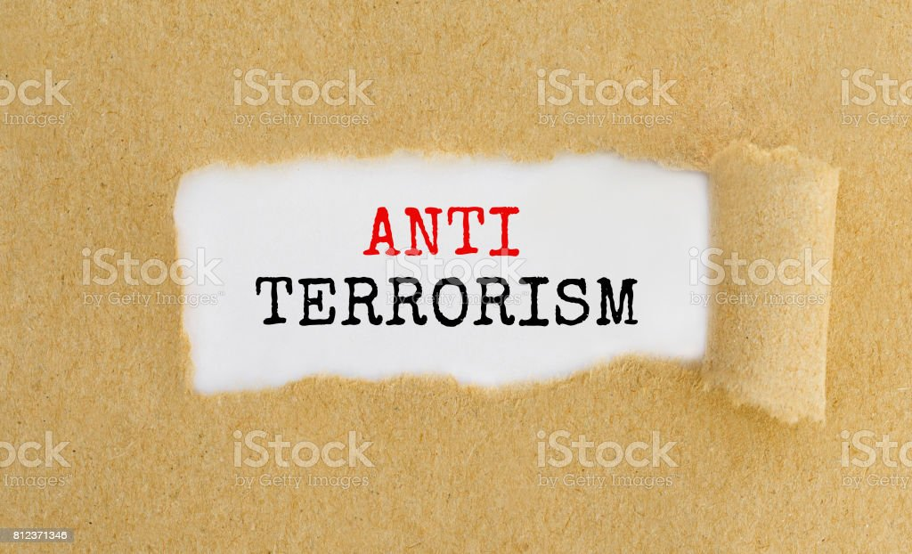 Text Anti Terrorism appearing behind ripped brown paper stock photo