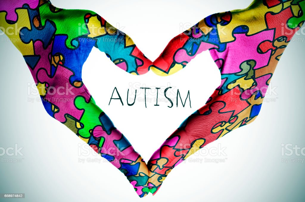 text autism and hands forming a heart with puzzle pieces stock photo