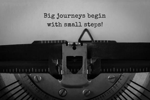 text groß reisen beginnen mit kleinen schritten auf retro-schreibmaschine getippt - bedeutungsvolle zitate stock-fotos und bilder