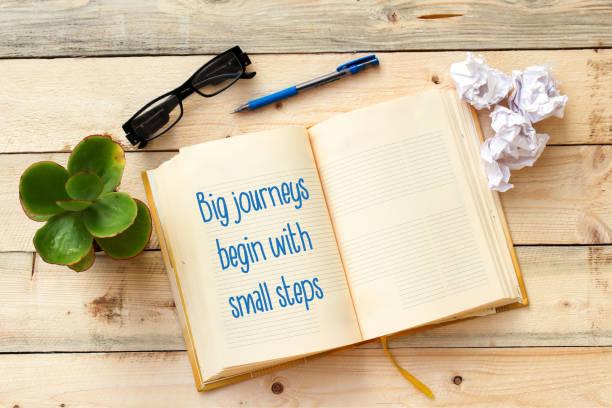 text groß reisen beginnen mit kleinen schritten typisierte offene notebook - bedeutungsvolle zitate stock-fotos und bilder