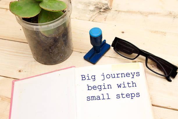 text große reisen beginnen mit kleinen schritten getippt offenes notebook - bedeutungsvolle zitate stock-fotos und bilder