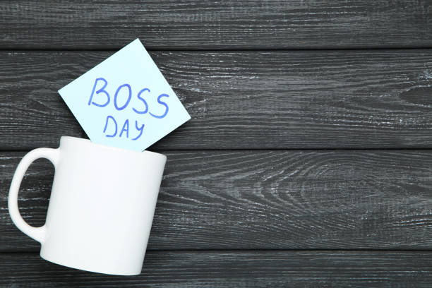 día del jefe de texto en pegatina y copa blanca sobre fondo de madera negro - boss's day fotografías e imágenes de stock