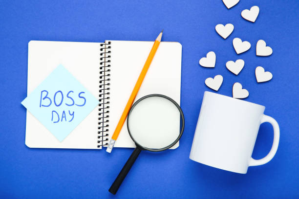 texto boss day en pegatina con copa, corazones, lupa y bloc de notas sobre fondo azul - boss's day fotografías e imágenes de stock
