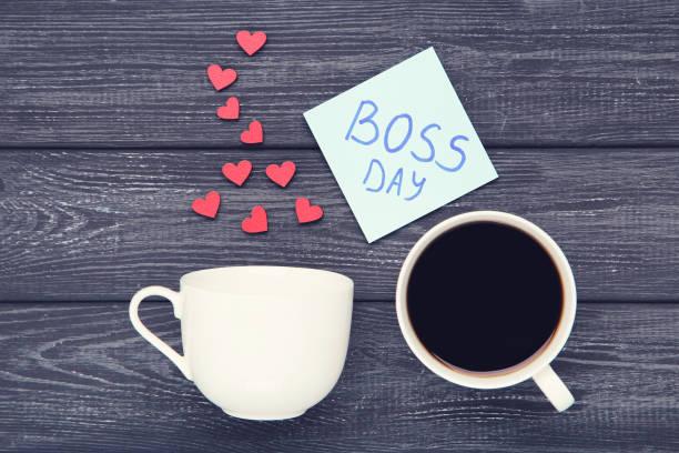 texto boss day en pegatina con tazas, corazones y café sobre fondo de madera negro - boss's day fotografías e imágenes de stock
