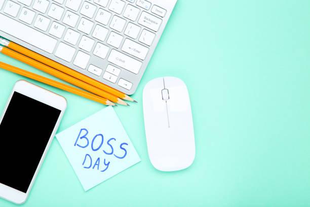 día del jefe de texto con lápices, teléfono inteligente, ratón y teclado sobre fondo azul - boss's day fotografías e imágenes de stock