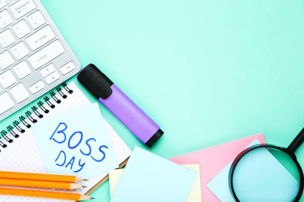 día del jefe de texto con pegatinas, lupa y bloc de notas sobre fondo azul - boss's day fotografías e imágenes de stock