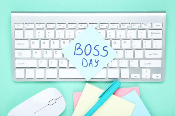 día del jefe de texto con pegatinas, ratón y teclado sobre fondo azul - boss's day fotografías e imágenes de stock