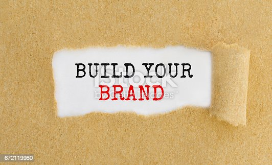 874270826 istock photo Text Build Your Brand appearing behind ripped brown paper. 672119980