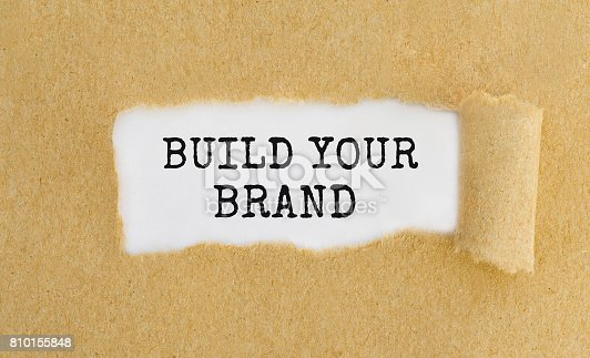 874270826 istock photo Text Build Your Brand appearing behind ripped brown paper. 810155848
