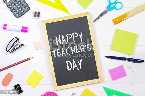 istock Text chalk on a chalkboard: Happy Teacher's Day. School supplies, office, books, apple. 929818112